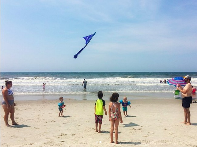 grandkids flying kite on the beach