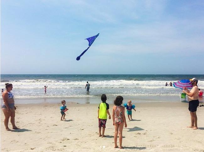 grandkids flying kite on the beach